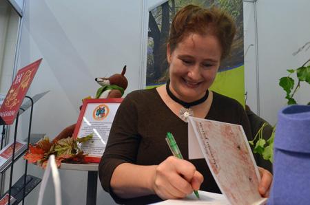 Runo-Kaarinan voittaja Pirkko Soininen pääsi viikonloppuna harjoittelemaan allekirjoitustaan. Kuvassa Soininen signeeraa teostaan viime vuoden Runo-Kaarinan voittajalle Aulis U. Lehtiselle. Kaarinan kaupunki oli kutsunut entiset voittajat vieraiksi kirjamessuille.