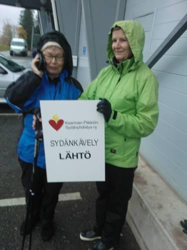 Tästä taulusta tiedät, että olet löytänyt lenkkiseuraa. Sydänkävelyn lähtötaulua pitelevät Marja-Helena Salmio (vas.) ja Arja Linnansuu.