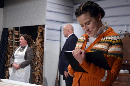 Kapteenin tytär (Juudit Rouhiainen) kirjoittelee päiväkirjaansa haaveistaan. Tyttären toiveisiin vastataan, kun tupaan pöllähtää nuori Lenin. Taustalla merikapteenia esittävä Hannu Pajunen ja kodinhoitajan roolissa Erica Selin. Kuva: Mika M. Niskanen.