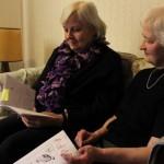 Terttu Teinikivi ja Laura Raitio selaavat yli 60 vuotta vanhoja lehtiä. Lehdessä kerrotaan muun muassa hiihtokilpailuista, perunajauhojen valmistuksesta ja korostetaan raittiutta.