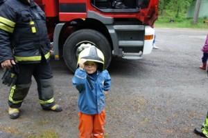 Pieni palon sammuttaja. Vilho Tähtinen, 3, sai kokeilla palomiehen kypärää ja pääsi myös käymään ison säiliöauton hytissä.