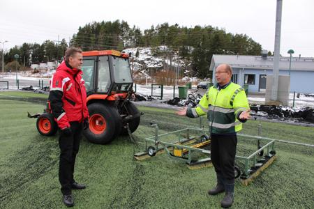 Tapio Svärd kertoo Jyrki Lapille tekonurmikentän hoidosta. Kentän harjaus nopeuttaa kentän sulamista, eikä energiaa kulu turhaan kentän lämmittämiseen. Kuva Aku Suomalainen