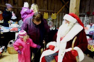 Sanni, 2 v, on päässyt juttelemaan joulupukin kanssa. Jännitystä lieventää, kun vieressä on myös isoäiti Marja Ruokonen.